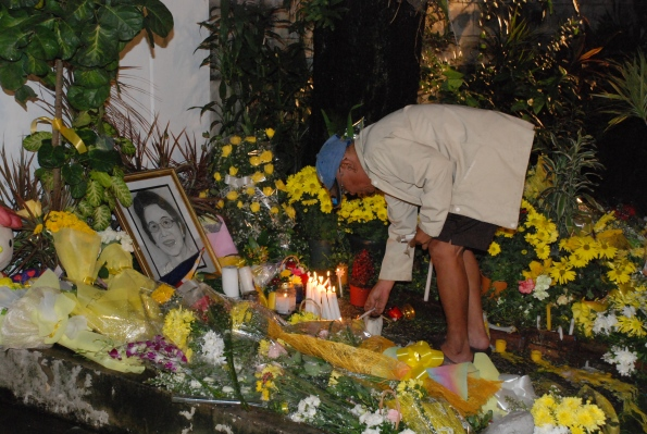 man tends to candles in front of cory's home at times street, quezon city